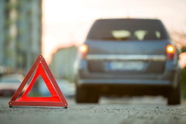 赤い緊急の三角形の一時停止の標識と街で壊れた車。