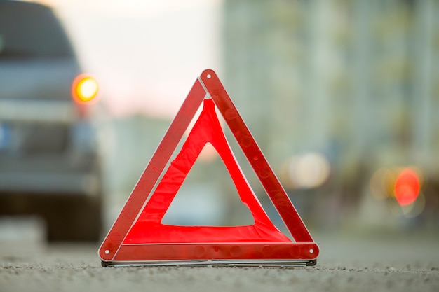 Red emergency triangle stop sign and broken car on a city street.
