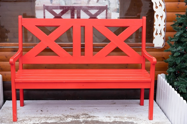 冬の外の赤い、空の木製ベンチ。