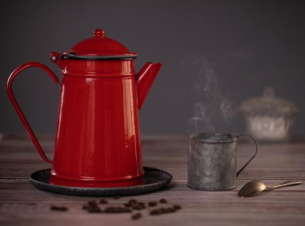 Красная эмалированная кофеварка с металлической чашкой дымящегося кофе