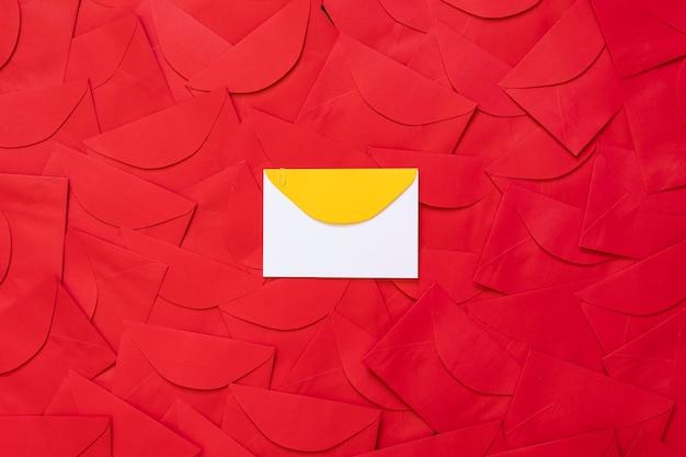 텍스트를 위한 공간이 있는 중앙에 노란색 세부 사항이 있는 흰색 카드가 있는 빨간색 봉투 배경.