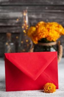Красный конверт и оранжевые цветы хризантемы на деревенском столе.