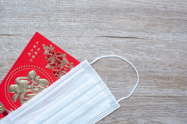 Red envelope or ang pao and medical face mask against coronavirus disease infection