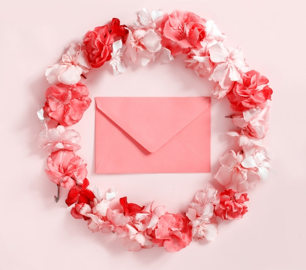 Red envelope in a frame of pink flowers over a pink background