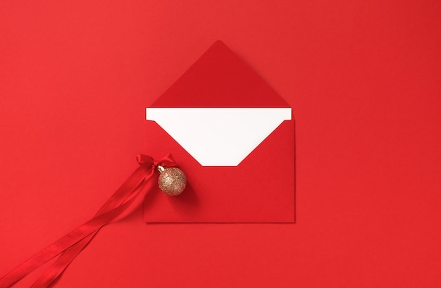 Red envelope and golden glitter christmas ball with bow from atlas ribbon