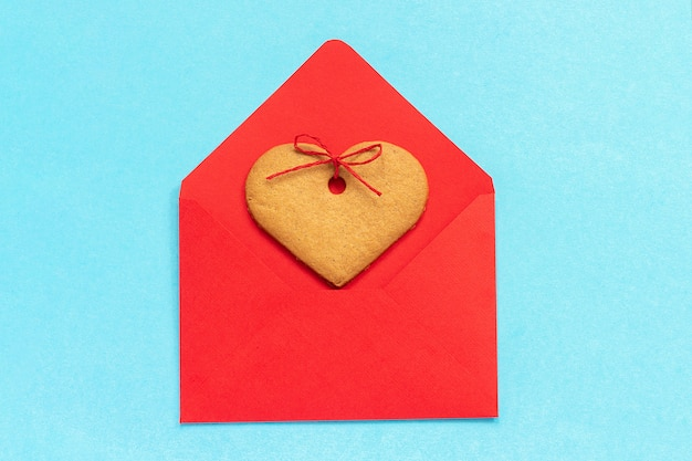 Red envelope and heart shaped ginger cookies on blue background