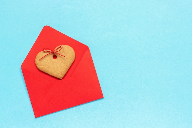 Red envelope and heart shaped ginger cookies on blue
