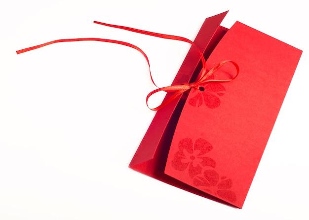 白い背景の上の天然繊維紙から作られた赤い封筒。クリッピングパスが含まれています。