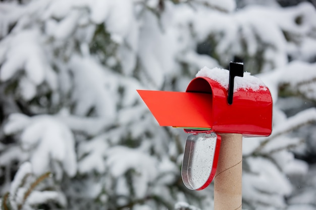 Red envelope in mailbox in a snow near pine tree in winter