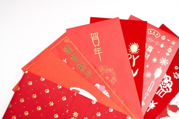 중국 설날 빨간 봉투 패킷, 중국 설날 흰색 배경에 '해피 뉴 이어'라는 문자가 있는 홍바오. 번역: 올해에 행운을 빕니다
