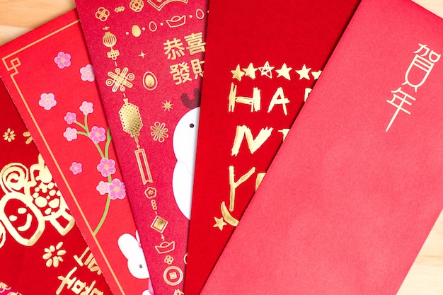 중국 설날 빨간 봉투 패킷, 중국 설날 나무 배경에 '해피 뉴 이어'라는 문자가 있는 홍바오. 번역: 올해에 행운을 빕니다