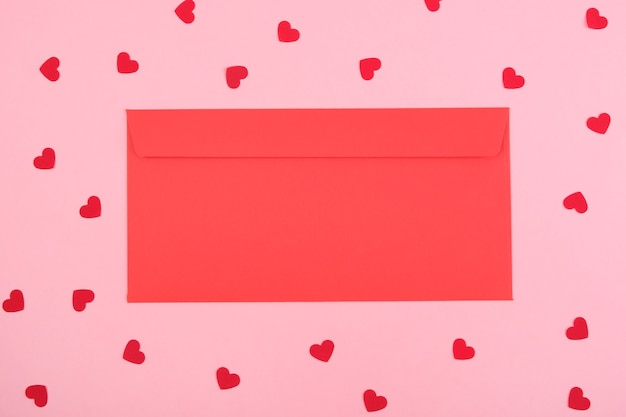 Red envelope on a pink background with hearts.top view. copy space. festive valentine's day concept.