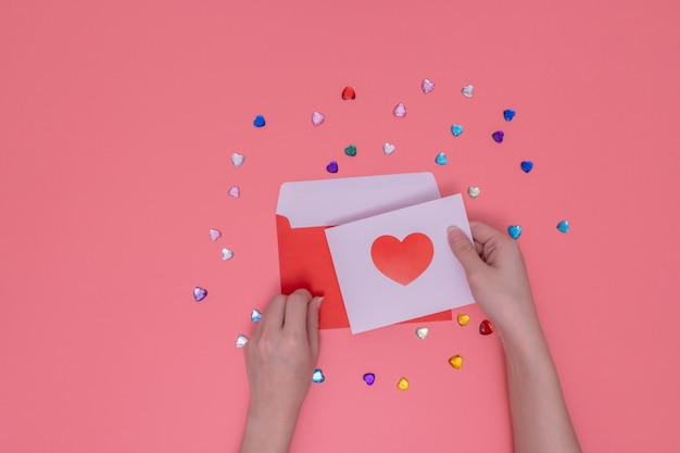 Red envelope and right hand holding a red heart in a white paper.