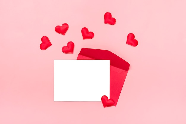 Red envelope, white writing paper,  hearts on pink background happy valentine's day concept