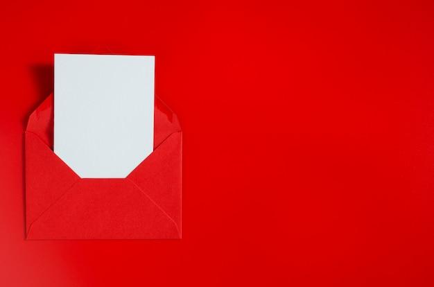 Красный конверт с чистой белой бумагой. день святого валентина фон. макет любовного письма.
