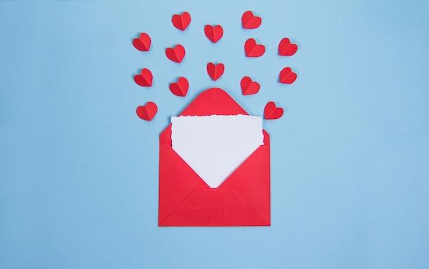 青い背景にテキスト用のカードが付いた赤い封筒、赤いバレンタインデーのハート、コピースパñe