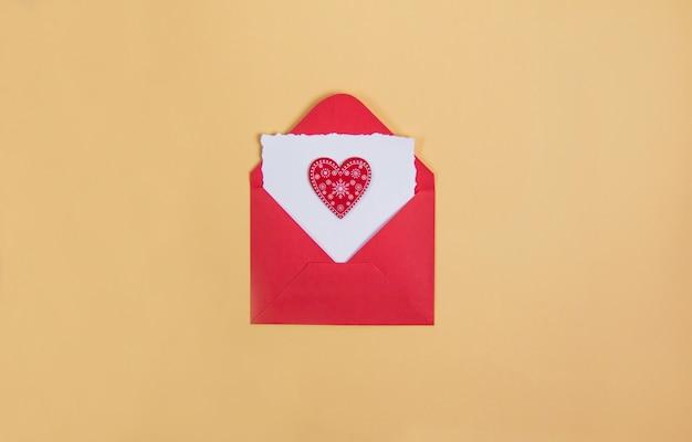 黄色の背景にテキスト用のカードが付いた赤い封筒、赤いバレンタインデーのハート、コピースパñe