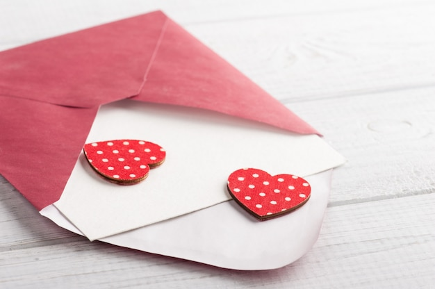 Red envelope with empty paper and red hearts