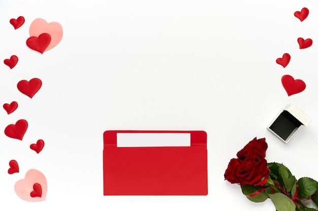 Red envelope with letter, bouquet of roses, many hearts and box for ring on white background. top view, flat lay