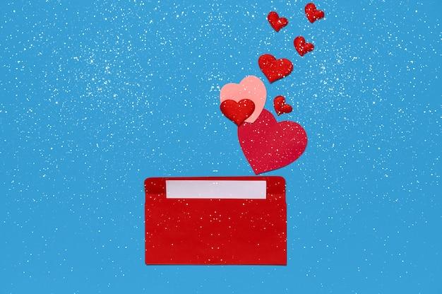Красный конверт с любовным письмом над синим фоном с множеством сердец и снежинок. из конверта вылетают сердечки. любовное письмо. концепция любви