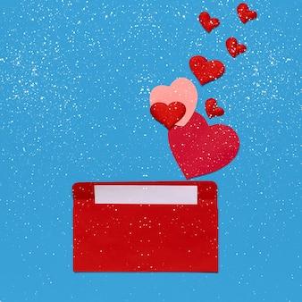Красный конверт с любовным письмом на синем фоне с множеством сердечек и снежинок