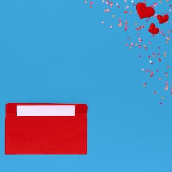 Красный конверт с любовным письмом над синим фоном с множеством сердец вокруг. из конверта вылетают сердечки. любовное письмо. концепция любви