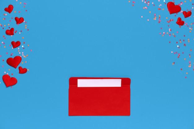 주위 많은 마음과 파란색 배경 위에 연애 편지와 함께 빨간 봉투. 하트가 봉투에서 쏟아집니다. 연애 편지. 사랑 개념