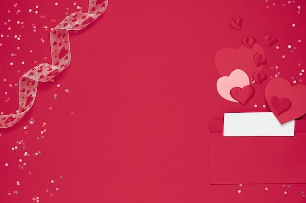 주위 많은 마음과 붉은 배경에 연애 편지와 함께 빨간 봉투. 하트가 봉투에서 쏟아집니다. 하트가 봉투에서 튀어 나옵니다. 연애 편지