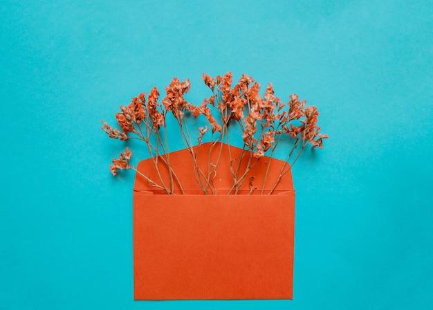 Красный конверт с красными цветами внутри на синем фоне. шаблон для информационных бюллетеней и других почтовых оформлений.