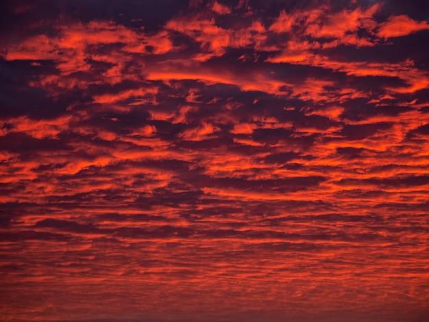 赤い夕方の空。夕暮れ時のカラフルな曇り空。空のテクスチャ、抽象的な性質の背景