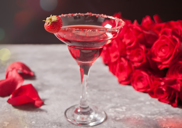 Red exotic alcoholic cocktail in clear glass and red roses