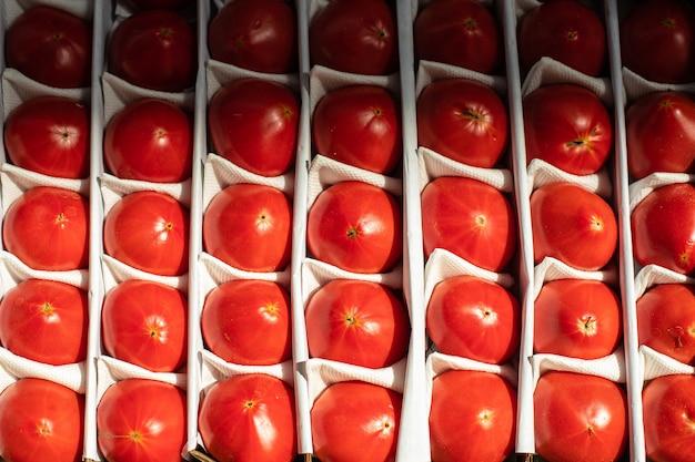 赤くて高価なトマトがなめらかで美しくレイアウトされています。買い手のために市場に出回っているトマト。