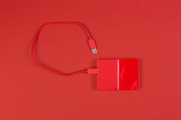 Red external harddrive disk on colored