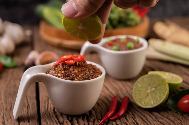 Паста red eye chili с лимоном и чили на деревянном полу.