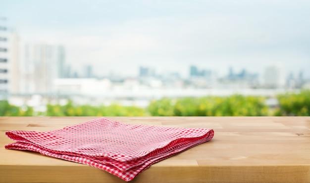 Красная ткань, ткань на деревянной столешнице на размытом городе и саду