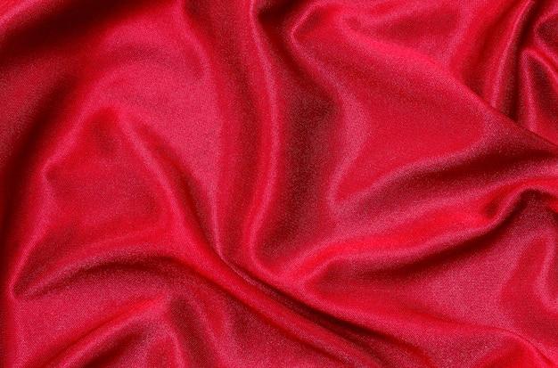 背景、美しいしわくちゃのシルクやリネンの赤い布の布のテクスチャです。