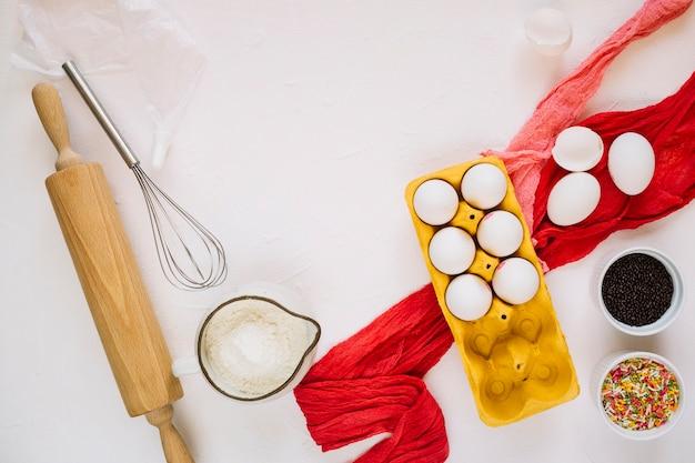 Tessuto rosso vicino a stoviglie e ingredienti