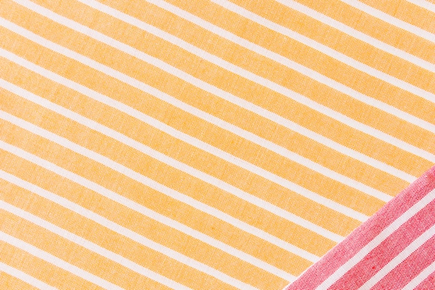 Red fabric on yellow and white stripes textile tablecloth