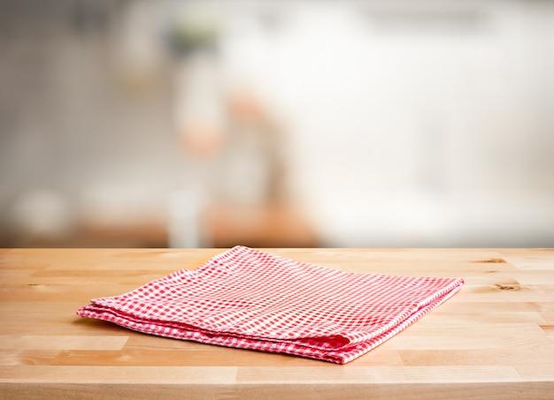 Красная ткань на деревянной столешнице на размытом фоне кухонной стойки