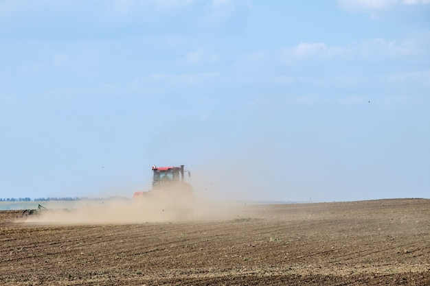 A red farm tractor in a cloud of dust cultivates the soil in the field