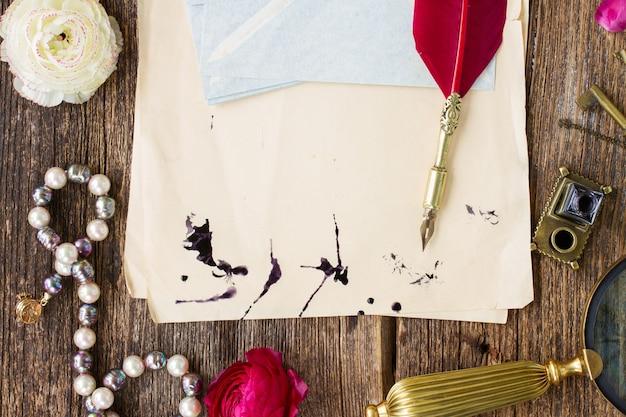 Красное перо на старой бумаге с чернилами