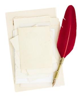 화이트에 고립 된 오래 된 페이지와 붉은 깃털 펜