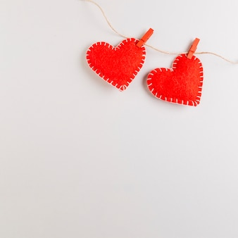 Red felt fabric hearts hanging on rope