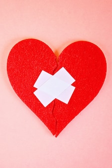 A red felt heart broken into two halves, glued together by plaster on a pink background.