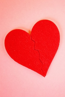 Red felt heart broken into two halves on pink background