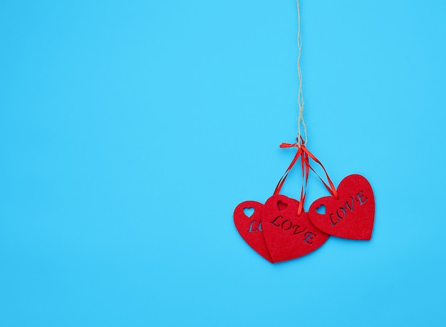 Red felt hearts hanging on a brown rope, blue background