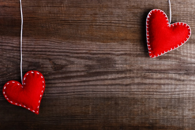 Red felt hearts on a wooden table. handmade blank for cards, copy space.
