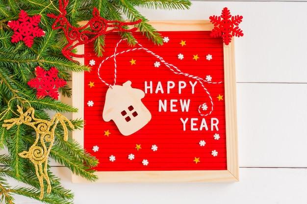 新年あけましておめでとうございますのテキストと白い木のおもちゃの家と白い木の背景に砂糖の小枝が付いている赤いフェルトのレターボード。冬休みのお祝いグリーティングカード。