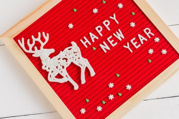 新年あけましておめでとうございますのテキストと白い背景に白い鹿と砂糖の小枝が付いた赤いフェルトのレターボード。冬休みのお祝いグリーティングカード