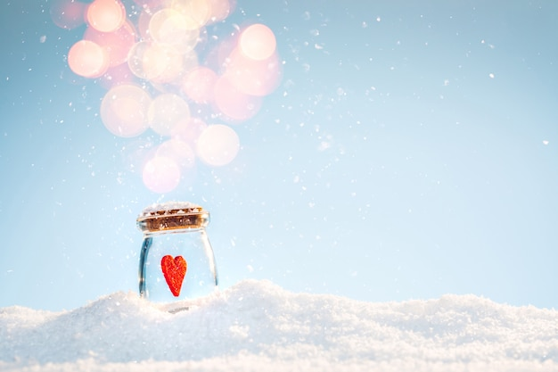 Red felt luminous heart in a jar on the snow in a winter sunny day. valentine's day concept